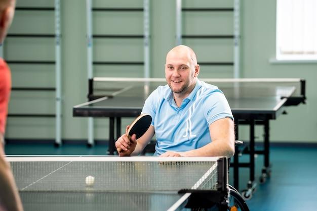 Volwassen gehandicapte man in een rolstoel tafeltennis spelen