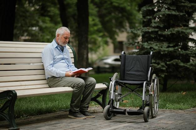 Volwassen gehandicapte man met rolstoel zit op een bankje in het zomerpark. verlamde mensen en handicap, handicap overwinnen. gehandicapte mannelijke persoon vrije tijd in openbare ruimte