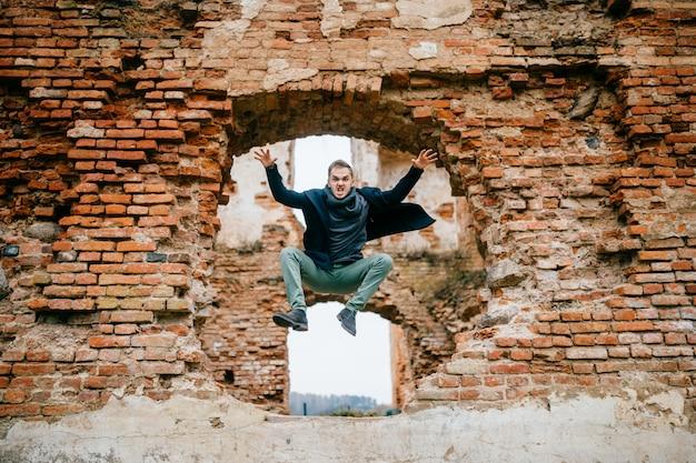 Volwassen gek boos ongebruikelijk opgewonden mannelijk portret. zakenman in vlucht beweging. jonge jongen die met grappige grappige expressieve oneven gezichtsemoties van bakstenen muur springt. vliegende persoon. sportactiviteit buiten