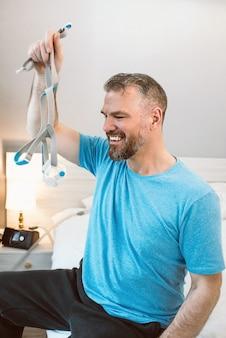 Volwassen gelukkige man met chronische ademhalingsproblemen met behulp van cpap-machine zittend op het bed