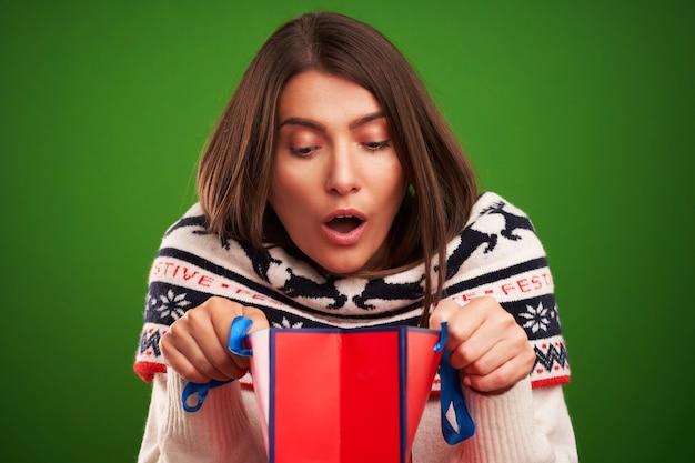 Volwassen gelukkige vrouw met kerstcadeau over groene achtergrond