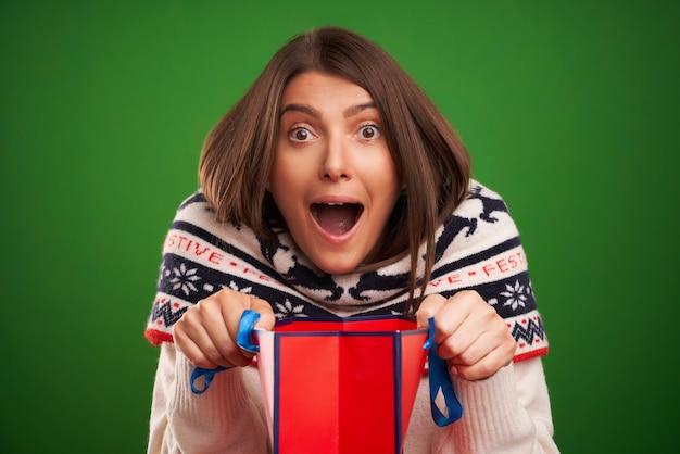 Volwassen gelukkige vrouw winkelen voor kerstcadeautjes over groene achtergrond