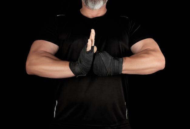 Volwassen gespierde atleet in zwarte kleding met teruggewonden handen met een zwart verband sloot zich aan bij zijn handen voor zijn borst
