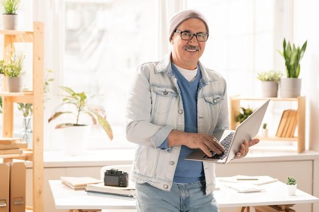 Volwassen glimlachende man in denim jasje, spijkerbroek en pullover permanent door bureau en typen op laptop toetsenbord in kantoor