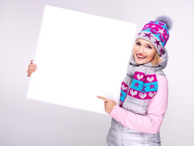 Volwassen glimlachende vrouw in warme bovenkleding houdt het witte bordje in handen en wijst erop