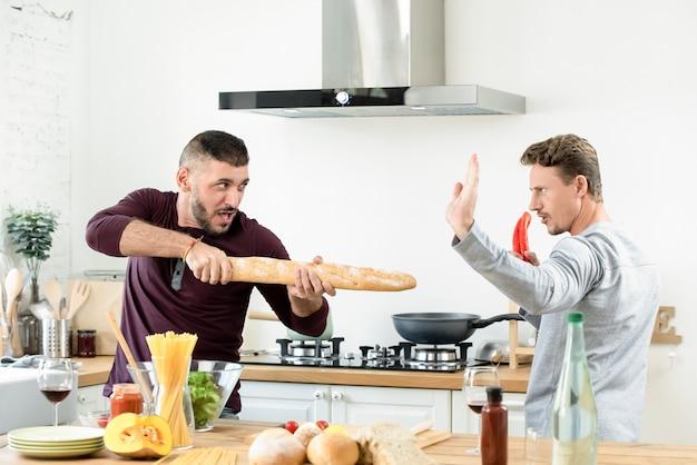 Volwassen homoseksueel mannelijk paar die rond met voedselingrediënten spelen in keuken