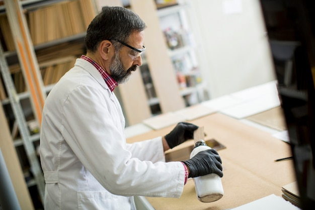 Volwassen ingenieur in het laboratorium onderzoekt keramische tegels