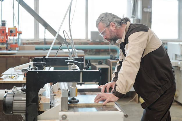Volwassen ingenieur van meubelfabriek buigen over industriële machine in werkplaats tijdens het bevestigen van werkstuk voor verdere verwerking
