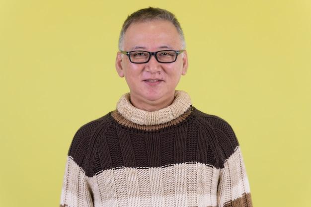 Volwassen japanse man met coltrui klaar voor de winter tegen chroma key met groene muur