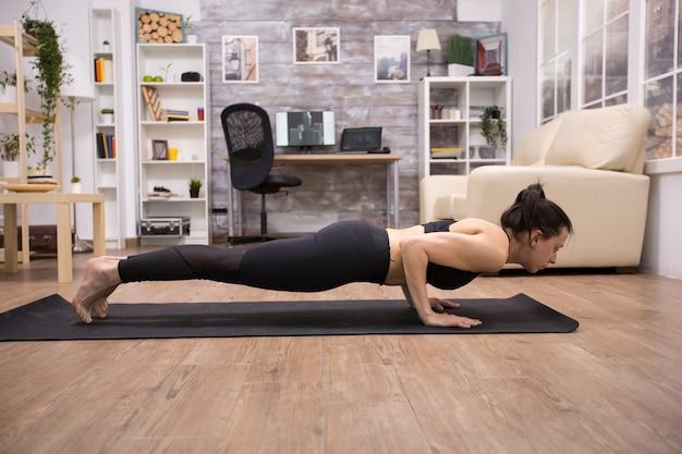 Volwassen jonge vrouw in sportkleding doet yoga pose voor een goede houding in de woonkamer.
