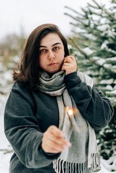 Volwassen jonge vrouw met wonderkaarsen op de achtergrond van het dennenbos van de winter