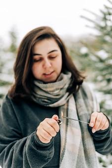 Volwassen jonge vrouw met wonderkaarsen op het dennenbos van de winter