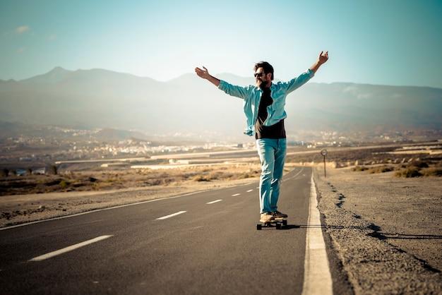 Volwassen jongeman die zich op een lange bordtafel beweegt op een lange asfaltweg en in de buitenlucht bergen op de achtergrond - concept van vrijheid en actieve mensen