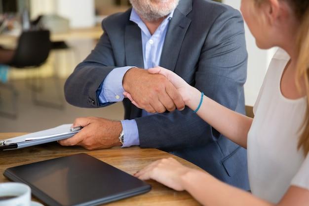 Volwassen juridisch adviseur ontmoeting met jonge klant bij co-working, documenten vasthouden en handen schudden