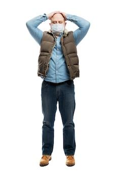 Volwassen kale man in een medisch masker houdt zijn hoofd in zijn handen. de financiële crisis en quarantaine tijdens de pandemie van het coronavirus. voorzorgsmaatregelen. volledige hoogte. geïsoleerd op een witte muur.