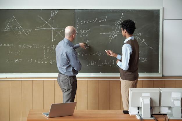 Volwassen kale professor en jonge student van gemengd ras bespreken oplossing van vergelijking door bord terwijl leraar wijst op een van zijn afgeleiden