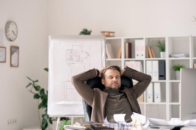 Volwassen kantoormedewerker in formalwear zittend in fauteuil bij bureau terwijl geconcentreerd op het werk of ontspannen tijdens pauze
