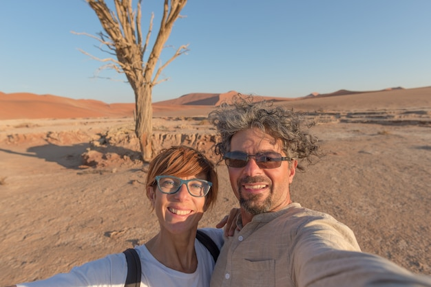 Volwassen kaukasisch paar die selfie in sossusvlei in de namib-woestijn, het nationale park van namib naukluft nemen