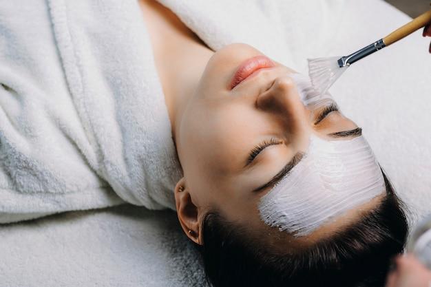 Volwassen kaukasisch wijfje dat huidverzorgingsmasker doet terwijl ze met gesloten ogen op kuuroordbed in een wellen-salon leunt.