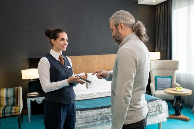 Volwassen klant van hotel gaat zijn handtekening zetten op het scherm van een tablet die wordt vastgehouden door een jonge vrouwelijke manager terwijl hij allebei tegen het bed in de kamer staat