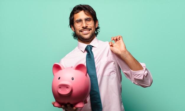 Volwassen knappe indiase zakenman met een spaarvarken