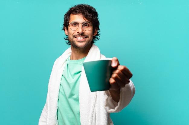 Volwassen knappe indier die badjas draagt en een kopje koffie drinkt