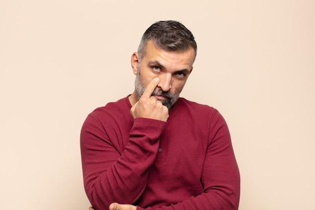 Volwassen knappe man die een oogje in het zeil houdt, niet vertrouwt, toekijkt en alert en waakzaam blijft