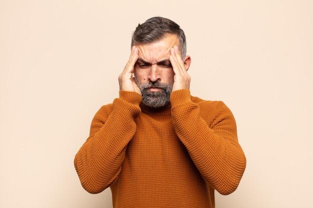 Volwassen knappe man die gestrest en gefrustreerd kijkt, onder druk werkt met hoofdpijn en last heeft van problemen