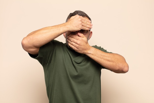 Volwassen knappe man die gezicht bedekt met beide handen en nee zegt tegen de camera! afbeeldingen weigeren of foto's verbieden