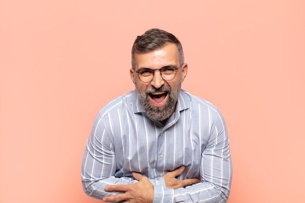 Volwassen knappe man die hardop lacht om een hilarische grap
