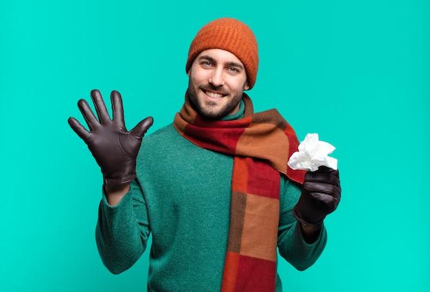 Volwassen knappe man die lacht en er vriendelijk uitziet, nummer vijf of vijfde toont met de hand naar voren, aftellend. ziekte en koude concept