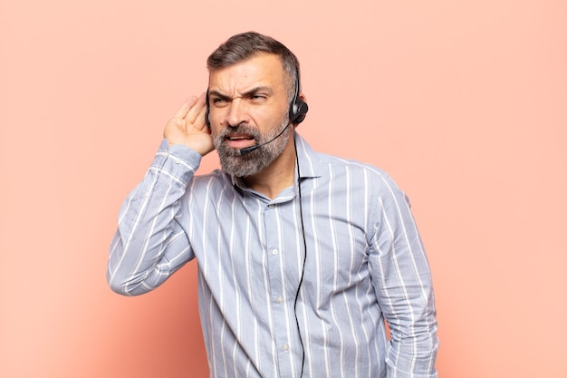 Volwassen knappe man die serieus en nieuwsgierig kijkt, luistert, probeert een geheim gesprek of roddel te horen, afluistert