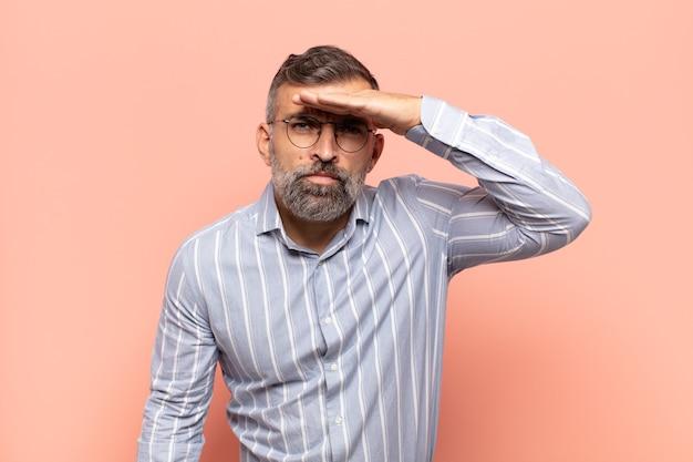Volwassen knappe man die verbijsterd en verbaasd kijkt, met hand over voorhoofd ver weg kijkend, kijkend of zoekend