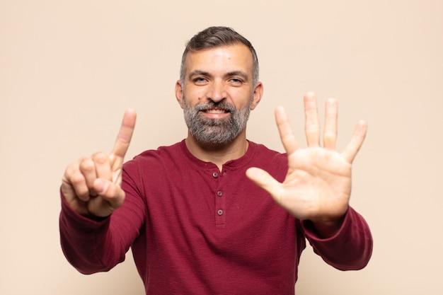 Volwassen knappe man die vriendelijk glimlacht en kijkt, nummer zes of zesde met vooruit hand toont, aftellend