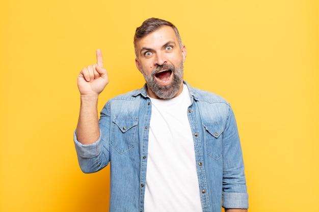 Volwassen knappe man die zich als een gelukkig en opgewonden genie voelt na het realiseren van een idee, opgewekt de vinger opstekend, eureka!