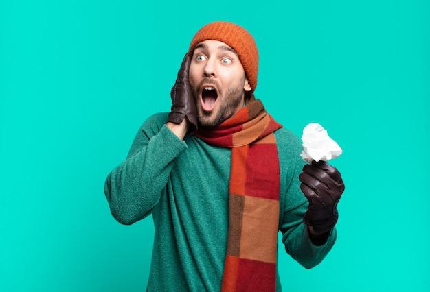 Volwassen knappe man die zich blij, opgewonden en verrast voelt, naar de zijkant kijkend met beide handen op het gezicht