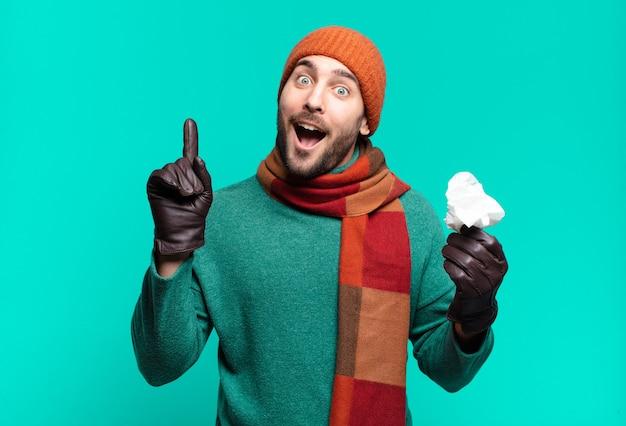 Volwassen knappe man die zich een gelukkig en opgewonden genie voelt na het realiseren van een idee, vrolijk de vinger opstekend, eureka!. ziekte en koude concept