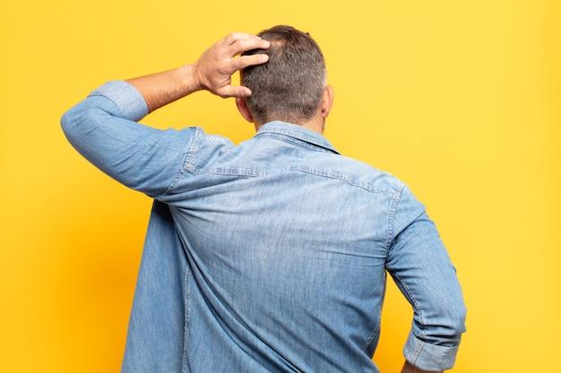 Volwassen knappe man die zich geen idee en verward voelt, een oplossing denkt, met de hand op de heup en de andere op het hoofd, zicht naar achteren