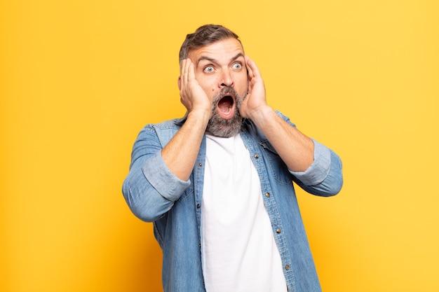 Volwassen knappe man die zich gelukkig, opgewonden en verrast voelt, opzij kijkend met beide handen op het gezicht