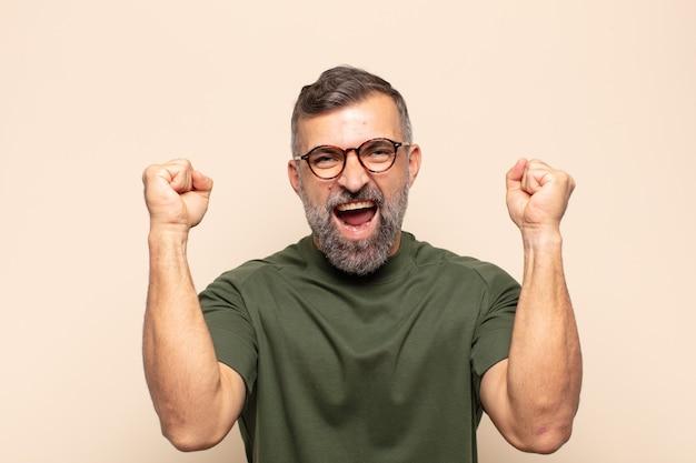 Volwassen knappe man die zich gelukkig, positief en succesvol voelt, overwinning, prestaties of veel geluk viert
