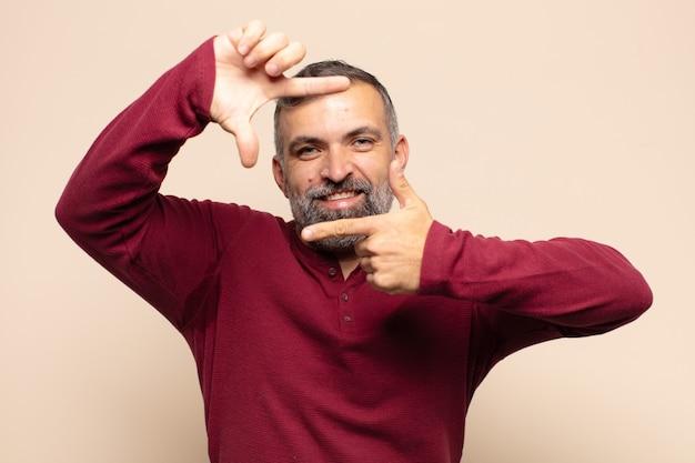 Volwassen knappe man die zich gelukkig, vriendelijk en positief voelt, lacht en een portret of fotolijst maakt met handen