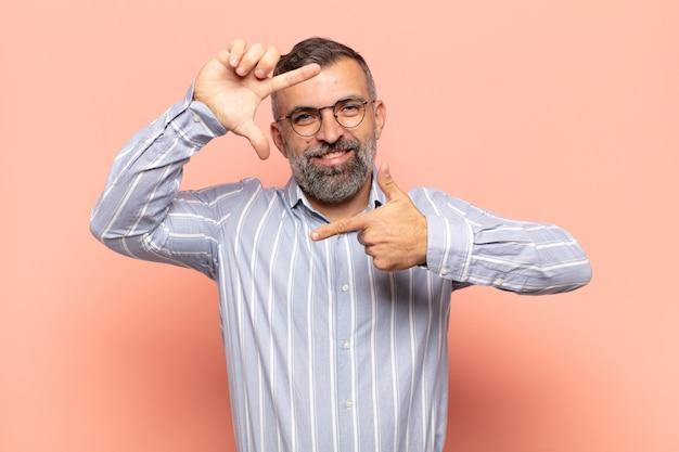 Volwassen knappe man die zich gelukkig, vriendelijk en positief voelt, lacht en een portret of fotolijst met handen maakt