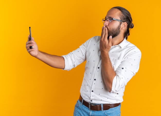 Volwassen knappe man met een bril die een mobiele telefoon vasthoudt en kijkt die een klapkus verzendt die op een oranje muur is geïsoleerd