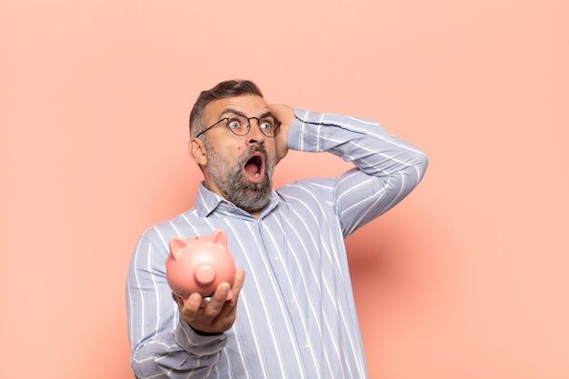 Volwassen knappe man met open mond, die geschokt en geschokt kijkt vanwege een vreselijke fout, zijn handen opheft