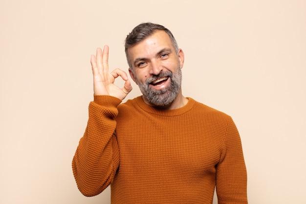 Volwassen knappe man succesvol en tevreden gevoel, glimlachend met wijd open mond, goed teken met hand maken