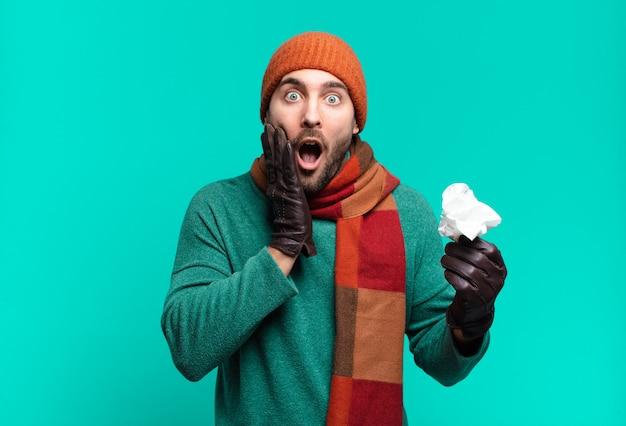 Volwassen knappe man voelt zich geschokt en bang, ziet er doodsbang uit met open mond en handen op de wangen. ziekte en koude concept