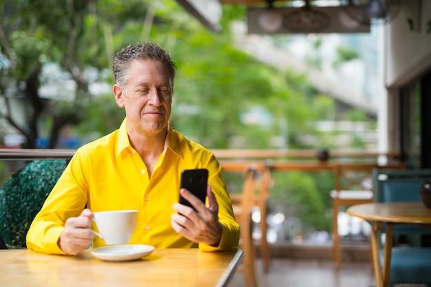 Volwassen knappe man zit in coffeeshop tijdens het gebruik van mobiele telefoon