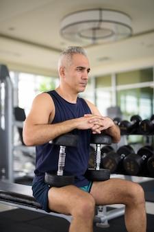Volwassen knappe perzische man die traint met halters en in de sportschool zit