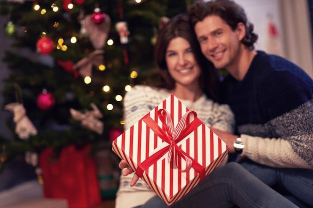 Volwassen koppel met cadeau boven kerstboom