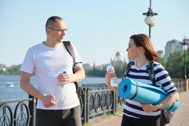 Volwassen lachende man en vrouw in sportkleding met rugzakken oefenmat wandelen in stadspark praten drinkwater uit de fles, actieve gezonde levensstijl van mensen van middelbare leeftijd